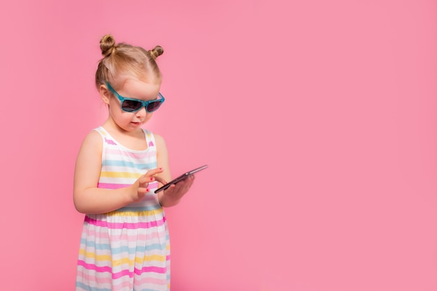 Addicted to phone little girl reading and sending sms. mobile phone digital device and children concept.
