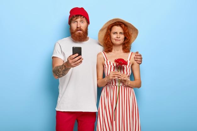 Озадаченный бородатый рыжий мужчина держит мобильный телефон и обнимает подругу