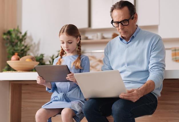 家に座ってインターネットサーフィン中に孫娘とデジタルガジェットを使用して中毒の引退した賢い男
