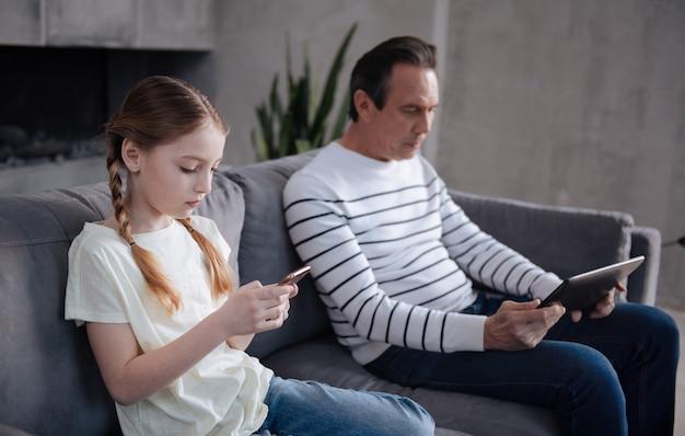 집에 앉아 인터넷 서핑을하면서 할아버지와 디지털 기기를 사용하는 중독 된 숙련 된 매력적인 소녀