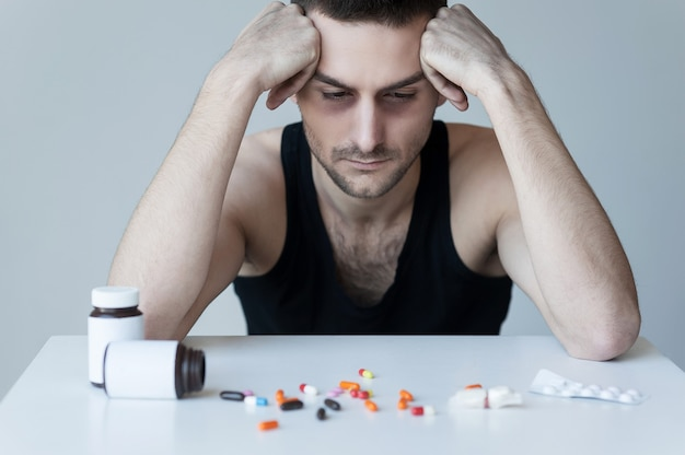 이 약에 중독되었습니다. 좌절된 청년은 탁자에 앉아 그 위에 놓인 약을 보고 있다