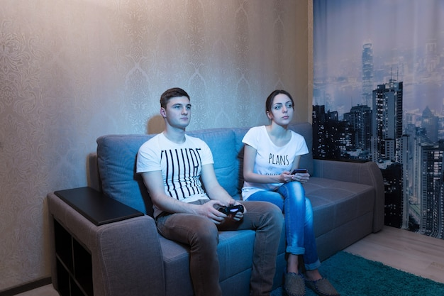 편안한 분위기에서 집에 있는 Tv 앞 소파에서 여자 친구가 그 과정을 감독하는 동안 중독된 젊은 남자가 앉아 비디오 게임을 하고 있다 프리미엄 사진