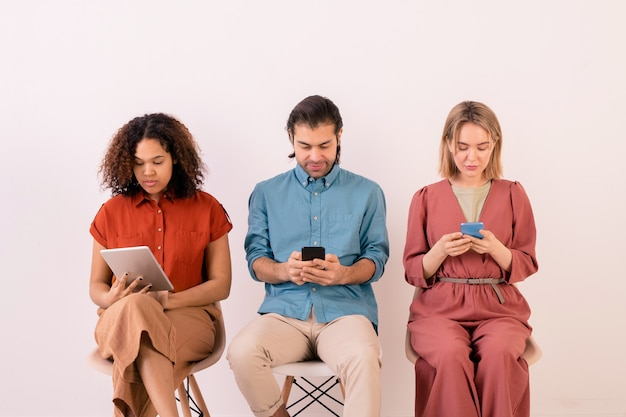 Addicted young multi-ethnic people sitting in line and focusing on social media while using gadgets