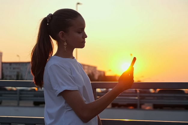 Addicted young teenage girl with ponytail holds smartphone