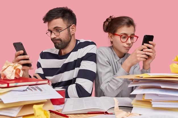 I giovani dipendenti si siedono gli uni agli altri, tengono in mano i telefoni cellulari, navigano sui social network, riposano dopo il lavoro, indossano gli occhiali