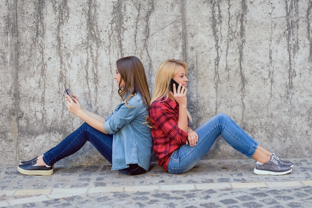 Addiction concept. two charming cute beautiful sweet charming brunette and blonde girls using modern smartphones sitting back to back spending time separately isolated on concrete gray wall background