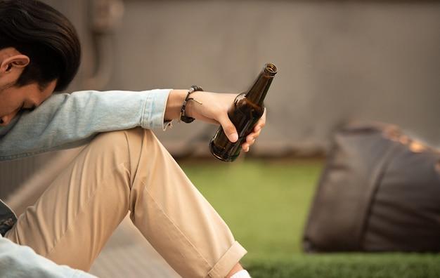중독 hungover 술에 취해 남자 맥주 병을 손에 앉아서 비활성 수면을 잡으십시오. 실업자 젊은 아시아 남자 재정 문제 희망 느낌 알코올 사용 고통 중지 고통.