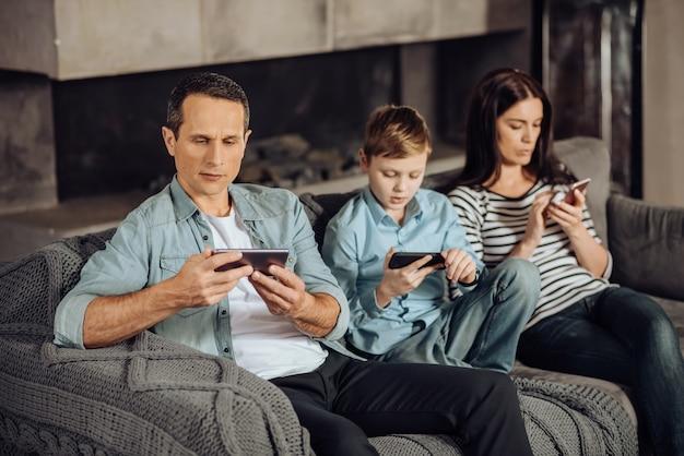 가제트에 중독. 소파에 앉아 서로에게 관심을 기울이지 않고 휴대 전화에 붙어있는 즐거운 젊은 가족