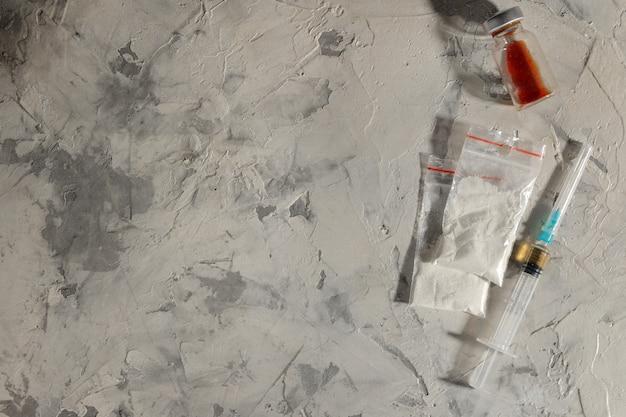 중독성 약물. 헤로인과 코카인은 밝은 콘크리트 배경이 아닙니다. 마약 중독의 개념입니다. 위에서 볼. 텍스트를 위한 공간