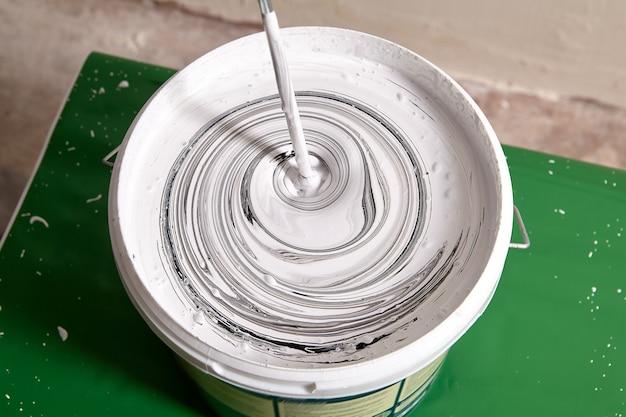 Добавление черного пигмента в белую краску для стен для смешивания в ведре с помощью электрического миксера до получения серого цвета.