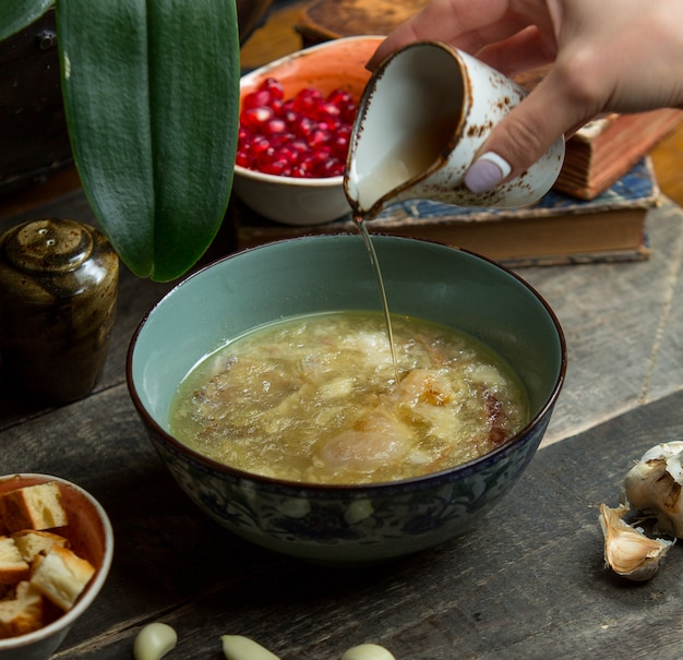 Adding broth into chicken soup in a blue authentic bowl