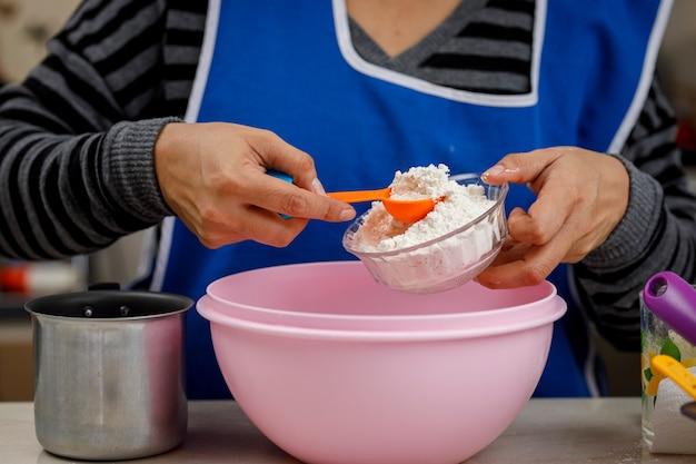 Добавление муки в миску с помощью мерной ложки, чтобы приготовить банановый блин.