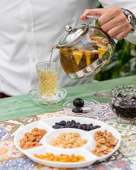 Adding fruit tea into glass with nuts around.