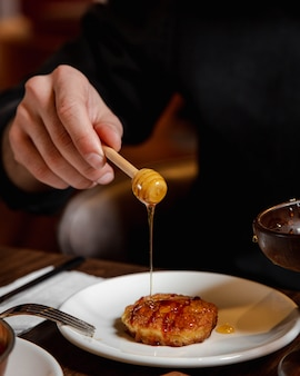 Adding honey to pancake inside white plate.