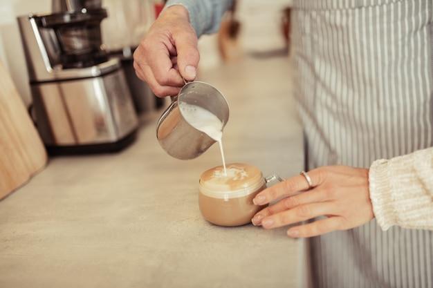 ミルクを追加します。コーヒーショップのゲストの手にコーヒーのカップにミルクを注ぐバリスタの手。