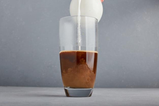 Добавляем молоко в кофе в стакане.