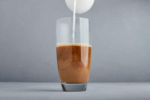カプチーノのグラスに牛乳を加える。
