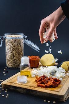 재료에 여자의 손으로 양파를 추가합니다. 스페인 렌즈 콩 요리의 수제 레시피