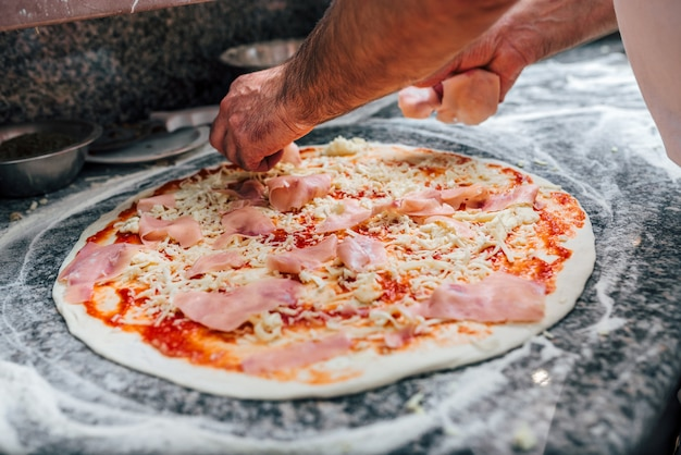Adding salami on the pizza. close-up.