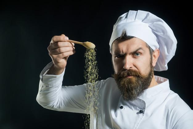 あごひげを生やした男性シェフがスパイスを振りかける手振りスパイス料理の調味料の肖像画を追加する