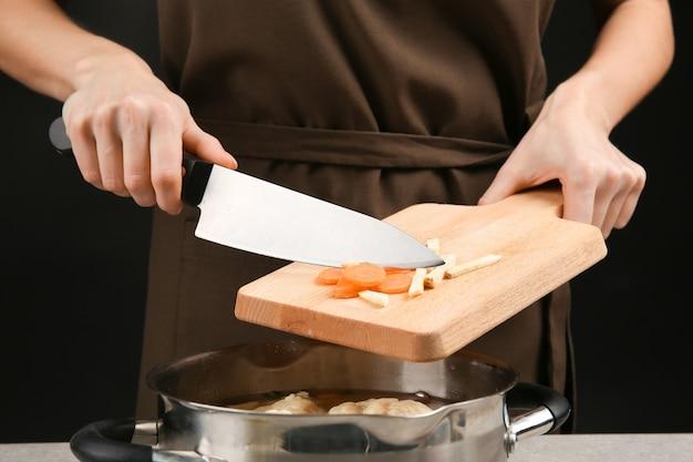 スライスしたにんじんとセロリをおいしい餃子と一緒に鍋に入れます