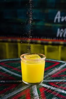 Добавление специй в апельсиновый коктейль в бокале для камня с большим кубиком льда и острым ободком на бокале