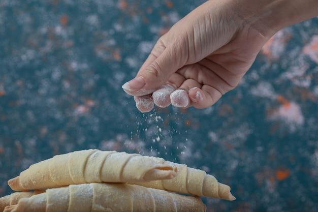 Aggiunta di zucchero in polvere sui biscotti mutaki caucasici.