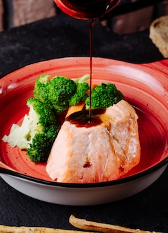 Adding teriyaki sauce to salmon steak with broccoli in pink bowl.