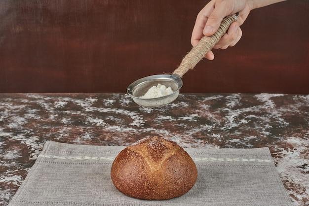 Aggiungere polvere bianca al panino di pane.