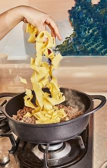 인터넷 레시피에 따라 볼로네제 스파게티 팬에 튀긴 다진 쇠고기에 스파게티를 추가합니다.