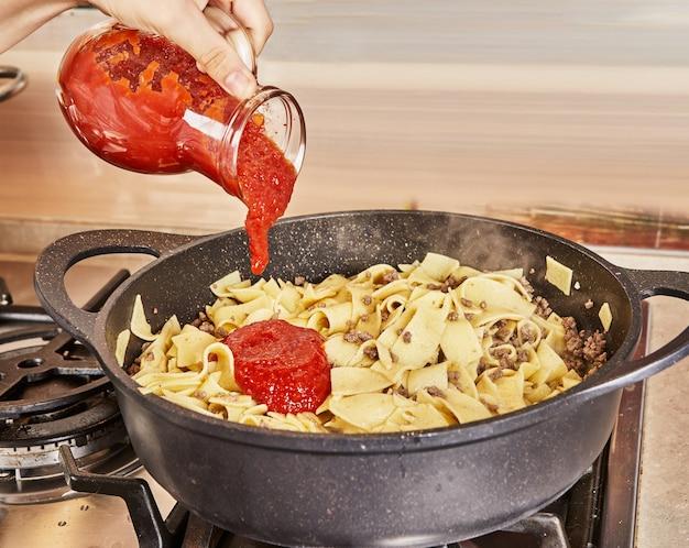 인터넷의 조리법에 따라 볼로네제 스파게티 팬에 튀긴 갈은 쇠고기 스파게티에 토마토 소스를 추가합니다.