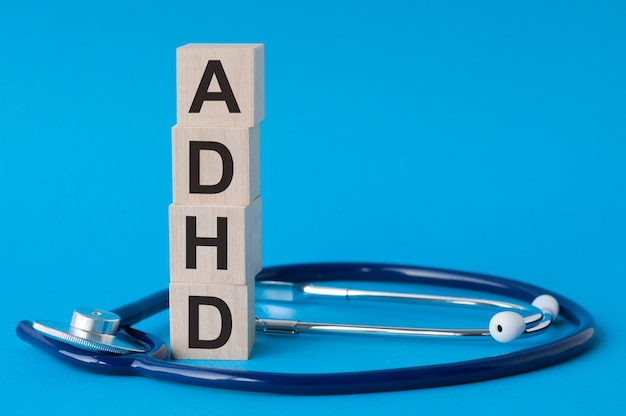 Adhd letters written on wooden blocks and stethoscope on light blue surface