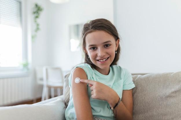 ワクチンまたは薬の注射後の腕の絆創膏、絆創膏-医療機器、ソフトフォーカスcovid-19ワクチン接種後の女性の腕の絆創膏