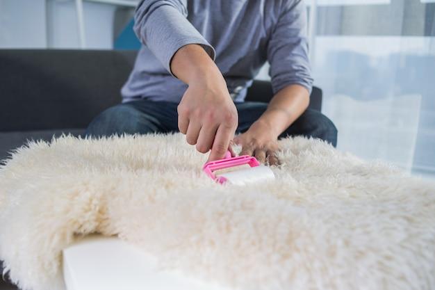 Rullo adesivo per la pulizia del tappeto di pecora. rullo di lint con maniglia rosa.