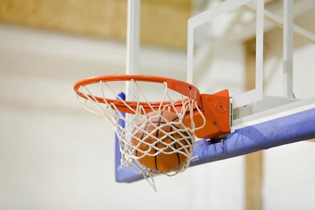 체육관에서 바구니를 치는 아디다스 농구 공