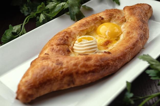 Adjar khachapuri、卵が付いた開いたパイ、白い皿の上。伝統的なジョージア料理