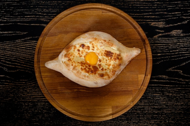 木製の背景の黒いプレートに卵とチーズの国民の伝統的な料理とアジャールのグルジアのハチャプリ。