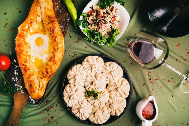 Adjarian khachapuri and khinkali served with sauce and salad