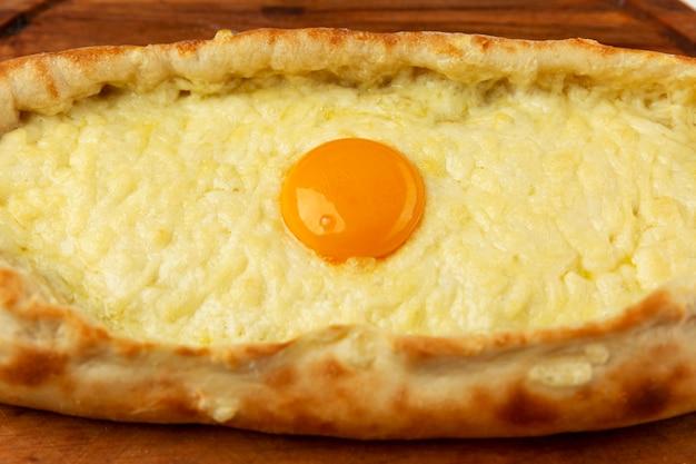 Хачапури по-аджарски с яйцом на деревянной доске. аппетитная тражиционная закуска. крупный план.