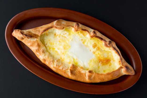 Adjarian khachapuri with eggs close up on black background