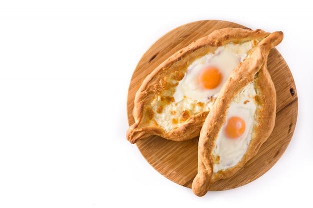 チーズと卵を白で隔離される伝統的なadjarianグルジアkhachapuri。上面図。