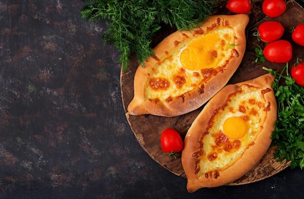 Adjarianのkhachapuriモッツァレラと卵のパイを開く。グルジア料理。