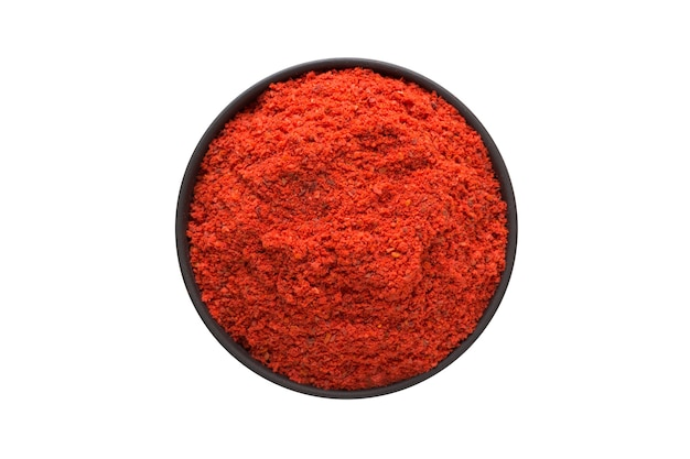 Adjika powder in clay bowl isolated on white background. seasoning or spice top view