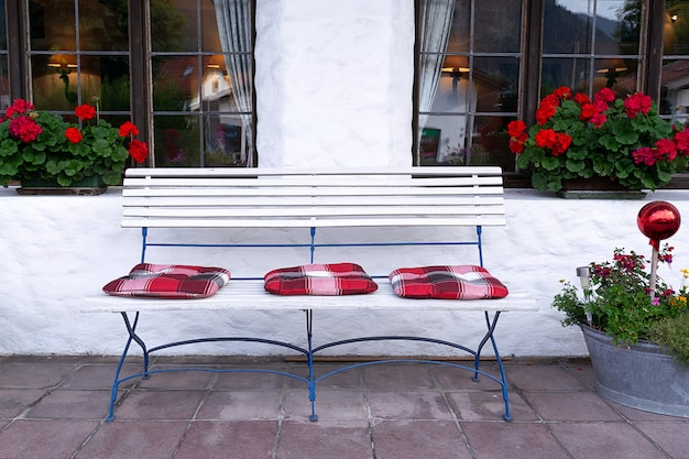 The adjoining territory is decorated with a white bench, flowers and bright pillows.