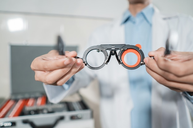 An adjustable axis trial frame is being held by a doctor in an eye clinic with a doctor background and a storage box