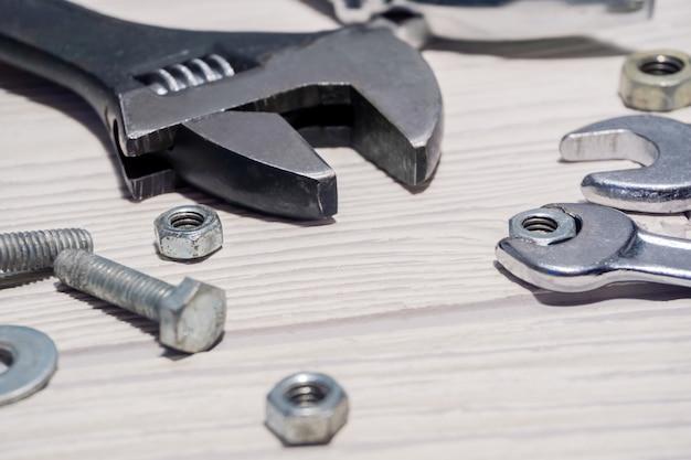 조정 가능한 스패너와 일반 렌치, 너트 및 볼트가 테이블에 가까이 있습니다.