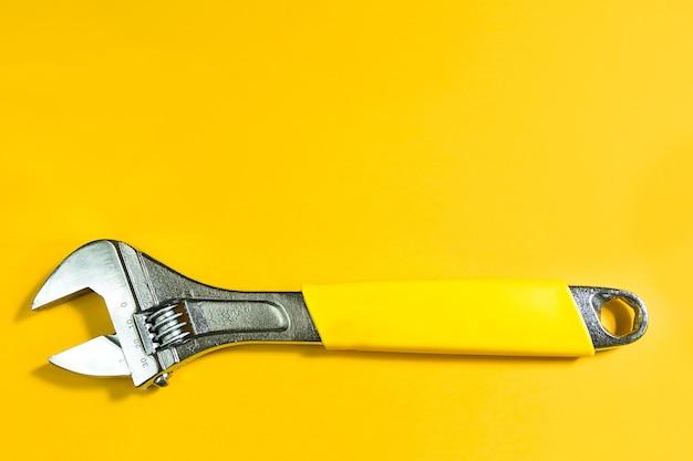 노란색 배경에 조정 가능한 범용 스패너 렌치입니다. 건설 및 수리, 배관 및 가전 제품, 파이프, 자동차, 주택. 자동차 정비사, 자물쇠 제조공, 배관공을 위한 도구입니다. 복사 공간