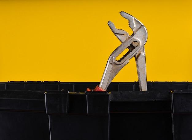 黄色に分離された黒いプラスチックツールボックスでモンキーレンチ
