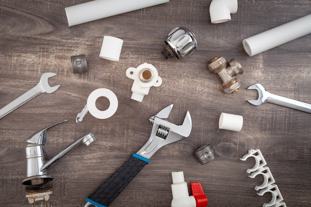 Adjustable wrench, plumbers tools and materials on the wooden background.