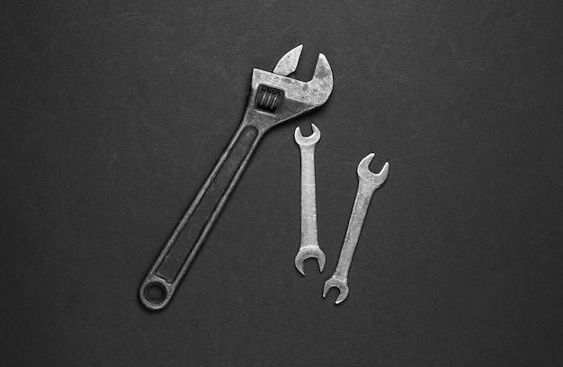 Adjustable wrench and wrench on a black background. work tool. top view